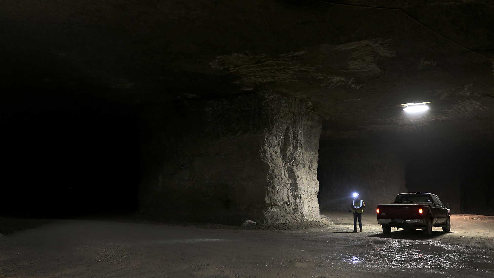 Foreman surveying progress in underground mine standing with headlamp on next to his truck