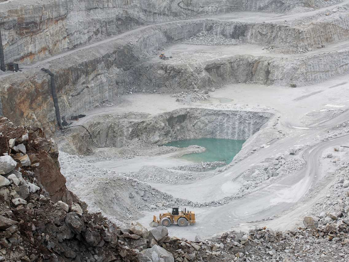Linwood Mining's outdoor mining pit with heavy equipment moving limestone